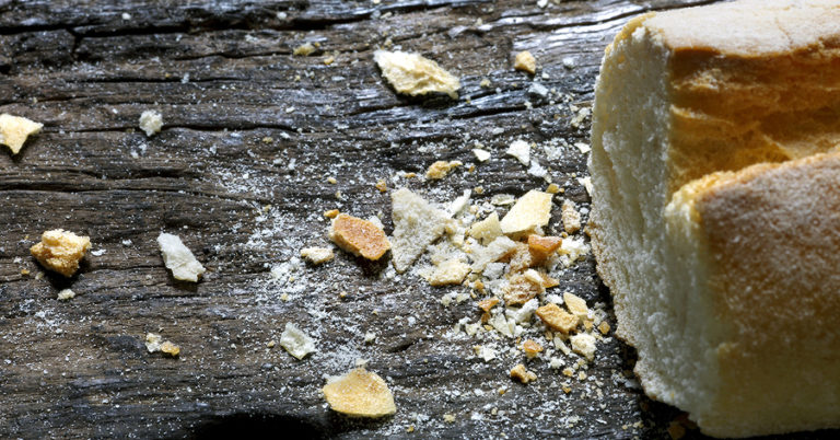 A photo of breadcrumbs on a table beside a French baguette (bread).