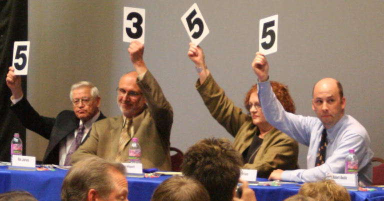 Judges scoring with numbers raised.