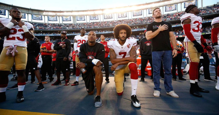 Colin Kaepernick and teammate kneeling in protest during the playing of the national anthem.