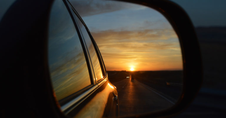 View of a sunset through a rear-view mirror.