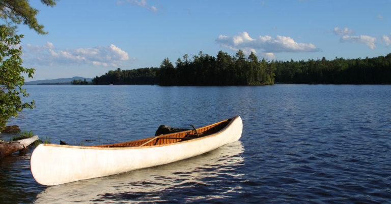 A photo of a canoe on a beautiful river with a blue sky above.