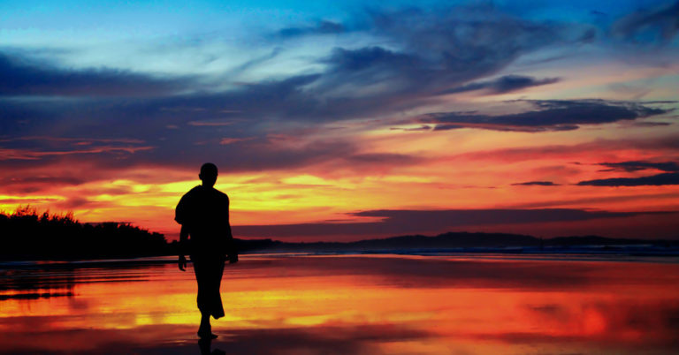 A man walking on the beach at sundown, symbolizing peace.